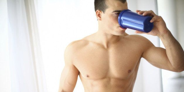 Muscular shirtless guy drinking protein shake after workout.