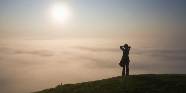 Lone figure on Glastonbury tor looking towards the Isle of Avalon shrouded by mist, Glastonbury, Somerset, England