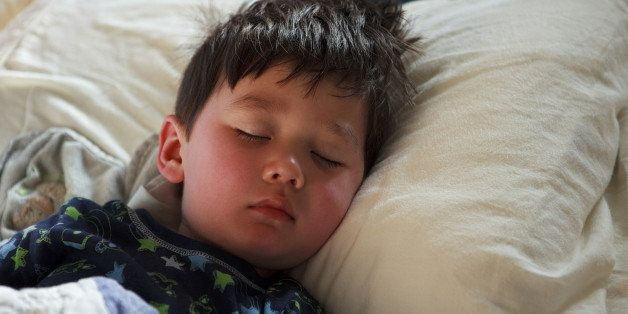 Half Asian Young Boy (3-4 years old) sleeping in bed wearing rocket pajamas with his head on a pillow Dreaming.