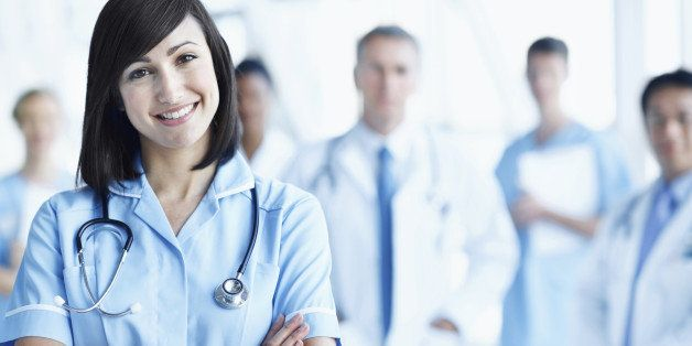Portrait of a young nurse with her team in the background