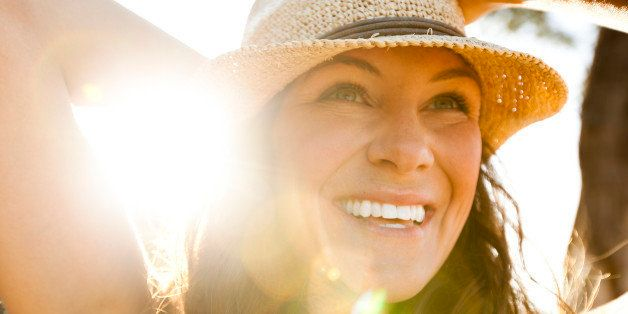A beautiful woman with a straw hat smiling.