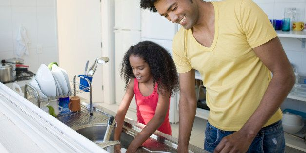 Father and daughter washing dishes.
