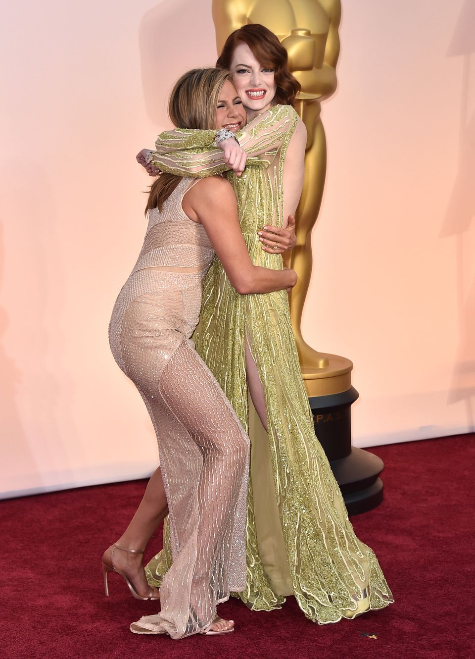 Jennifer Aniston, left, and Emma Stone arrive at the Oscars on Sunday, Feb. 22, 2015, at the Dolby Theatre in Los Angeles. (P