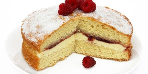 Home made Victoria sponge cake filled with butter cream and raspberry jam, topped with home grown raspberries, on a white plate with white background.