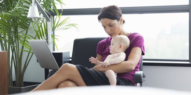 Woman holding baby using laptop