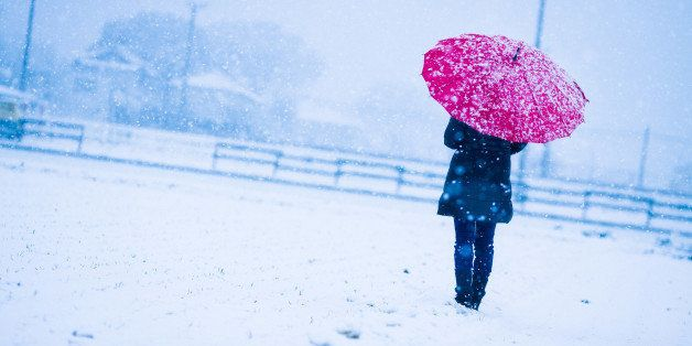 Woman holding a red umbrella on a snowy day.