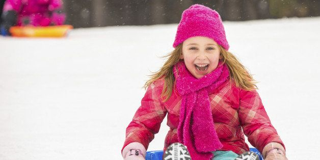 Happy girl expressing joy while sledding in the snow in winter.