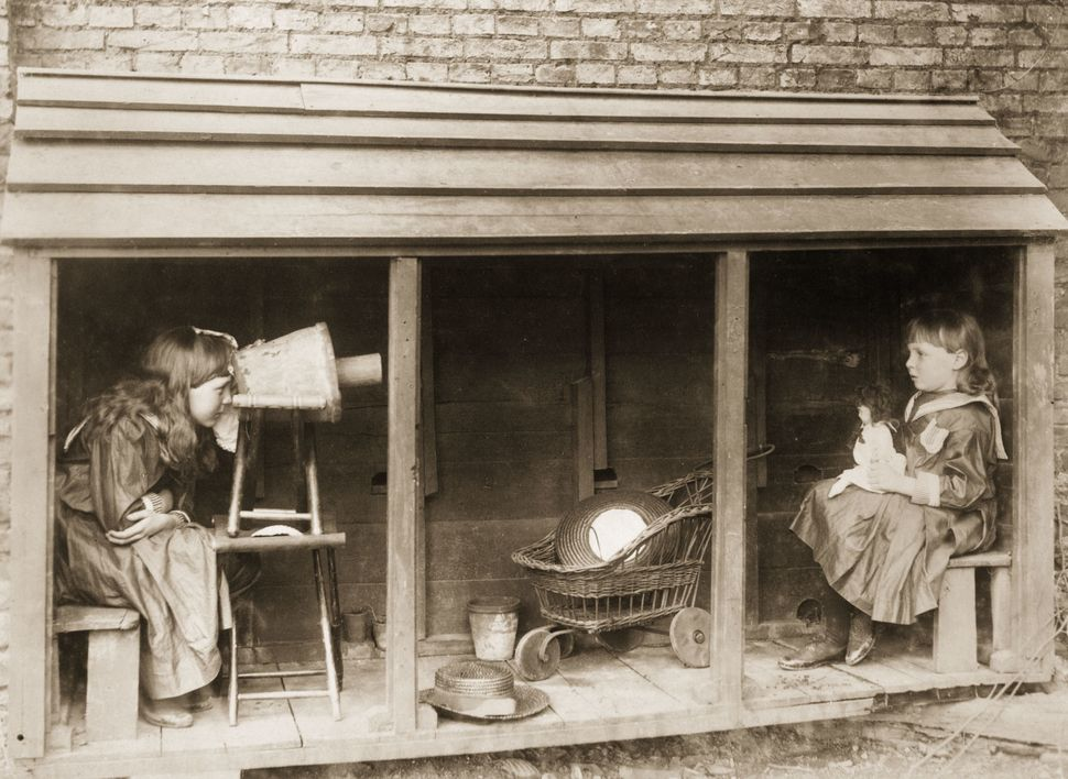 1887:  A little girl uses a camera made from a stool and a flowerpot to 'photograph' her friend.  (Photo by Rev F. C. Lambert