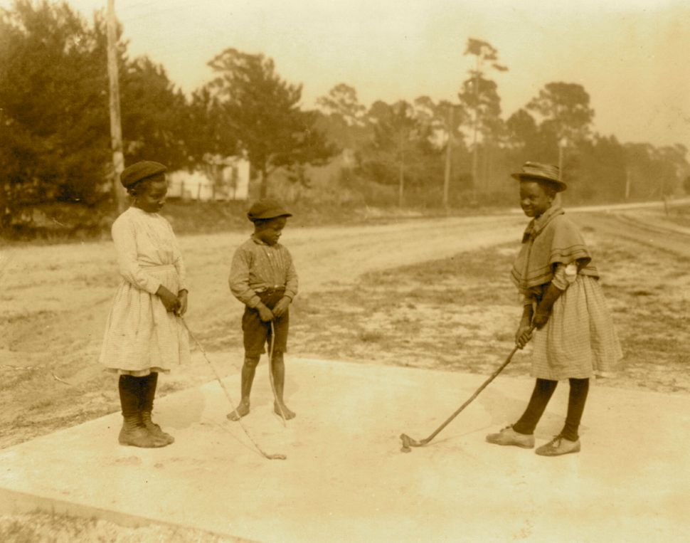 Circa 1905:  Three children playing golf with clubs made of sticks.  (Photo by Buyenlarge/Getty Images)