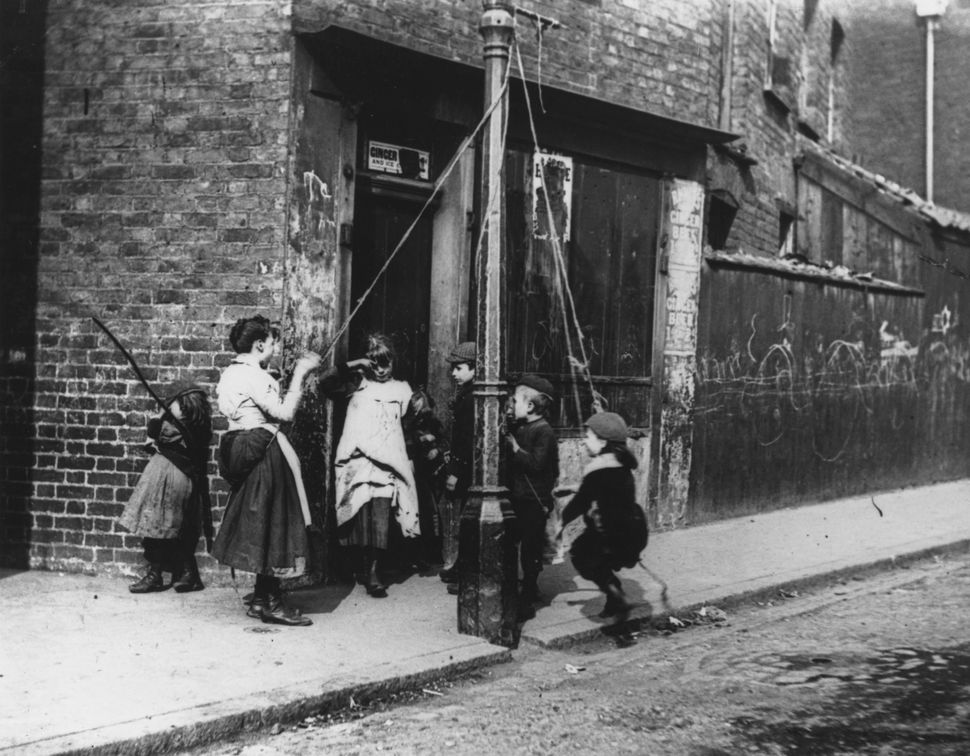 Circa 1892: Children living in the slums improvise a lamppost and some rope as a swing.   (Photo by Paul  Martin/Getty Images