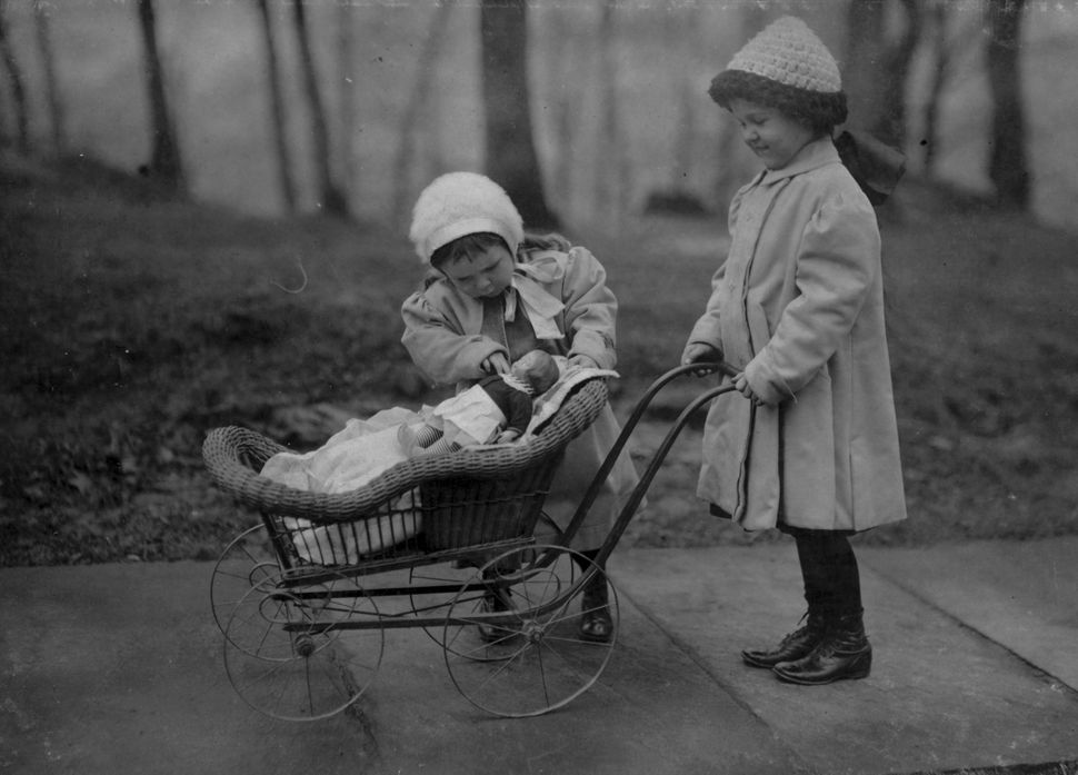 Two young girls play a Campbell Soup Kid doll, New York, New York, March 1912. One pushes it in a pram while the other looks
