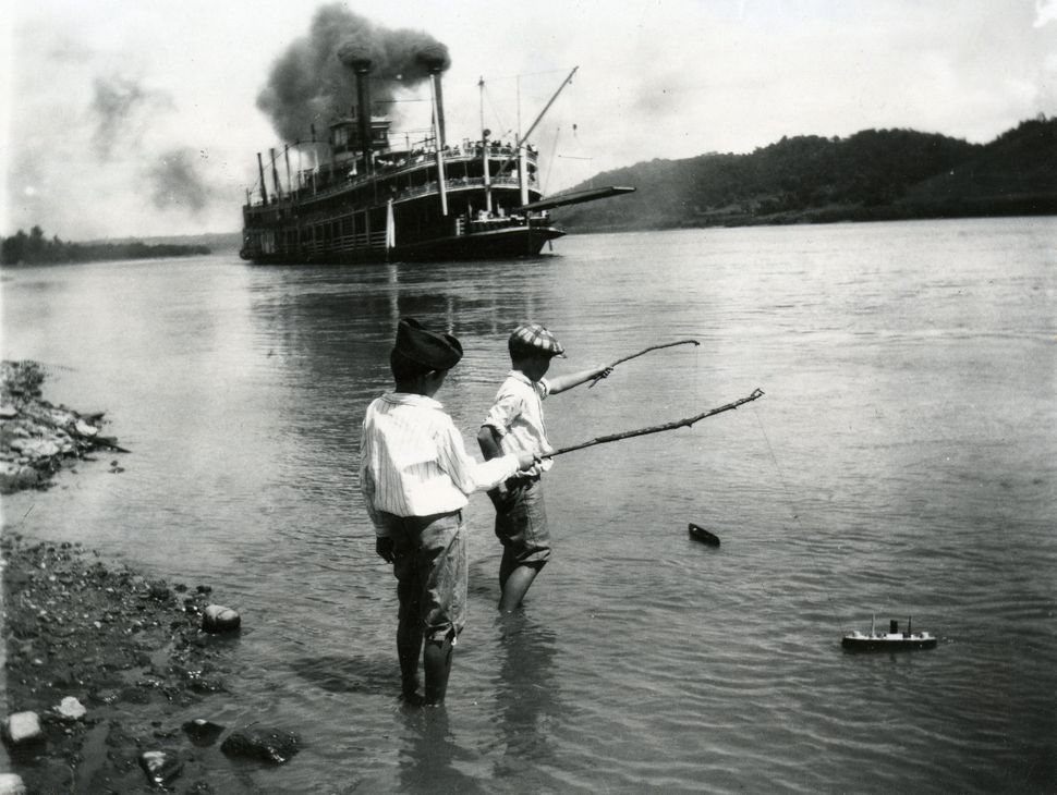 Children playing with toy boats on the river's edge as a steamboat passes in Rising Sun, Indiana, 1919. (Photo by Felix Koch/