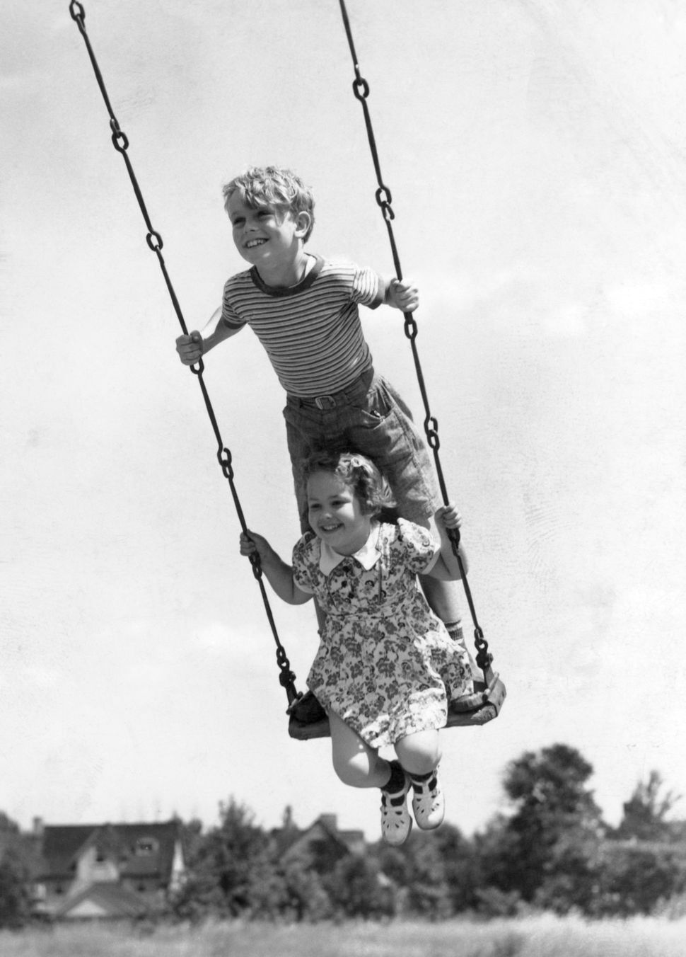 Circa 1930s:  Boy And Girl On Swing.  (Photo by H. Armstrong Roberts/Retrofile/Getty Images)