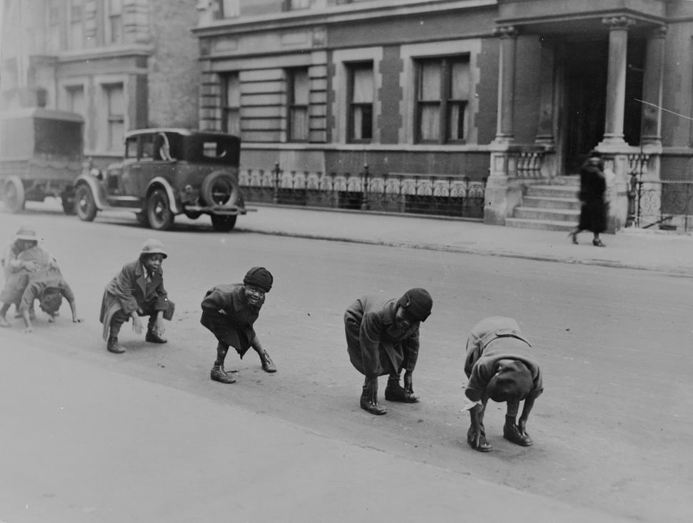 Circa 1935 Children playing a game of leap-frog in a street in Harlem, New York.   (Photo by Henry Guttmann/Getty Images)