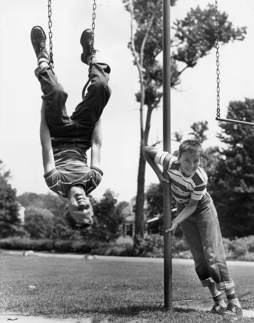Circa 1945:  One young boy hangs upside down on the rings of a playground swing set, as another boy leans against a pole next