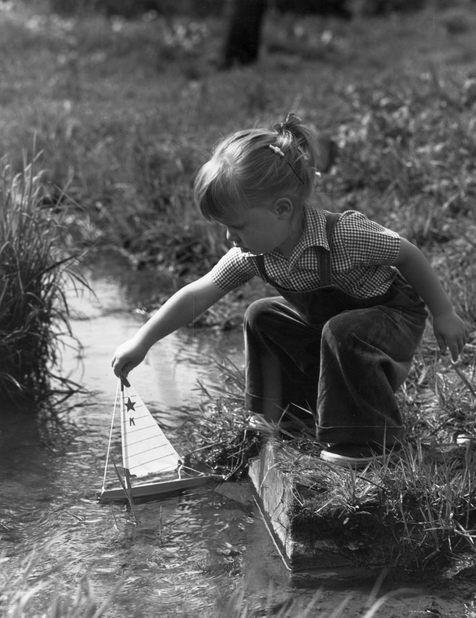 Circa 1945:  Full-length image of a young girl crouching on the grassy banks of a stream, holding the mast of a toy sailboat