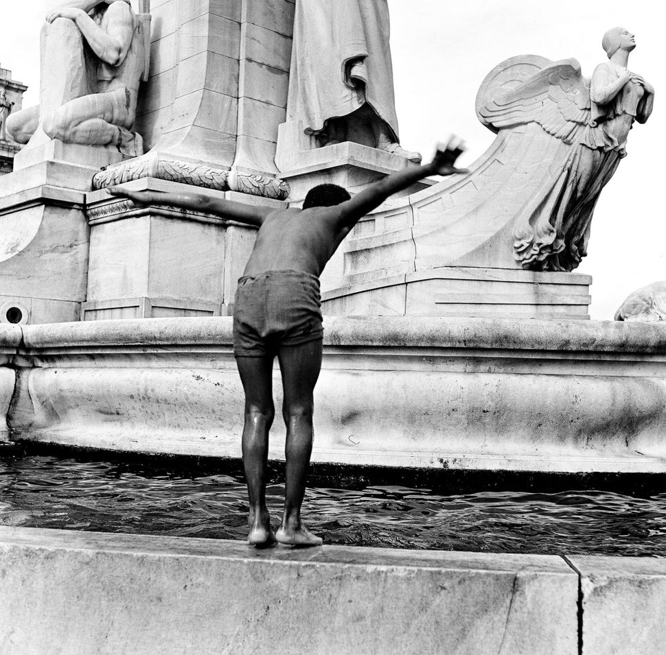 A young boy perched on the edge of a fountain prepares to jump into the water, Washington DC, 1948. (Photo by Rae Russel/Gett