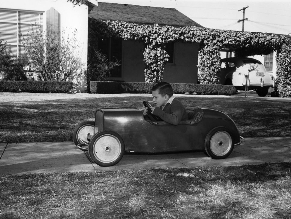 Circa 1953: Boy in a pedal car. Driving his pedal car on the pavement outside his house. (Photo by National Motor Museum/Heri