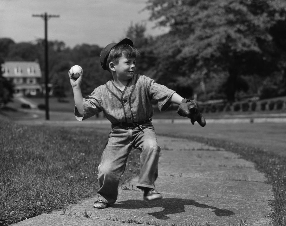 Circa 1955:  A young boy throwing a baseball on a sidewalk.  (Photo by Lambert/Getty Images)