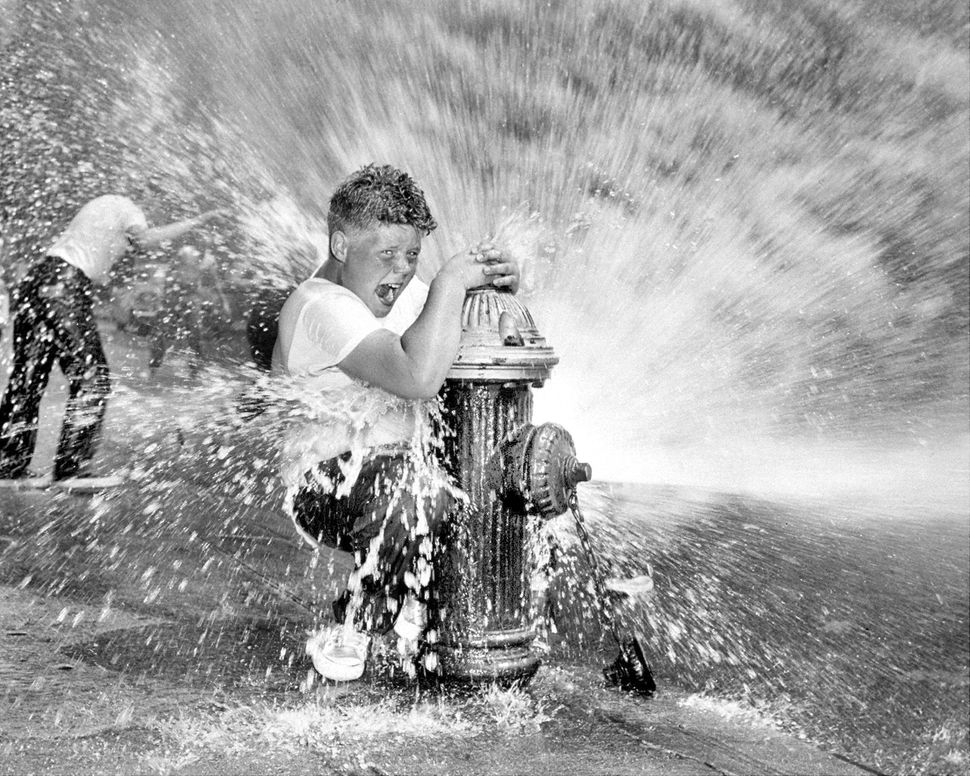 July 01, 1959:  Youngster playing in water from fire hydrant. Police are waging campaign against indiscriminate opening of hy