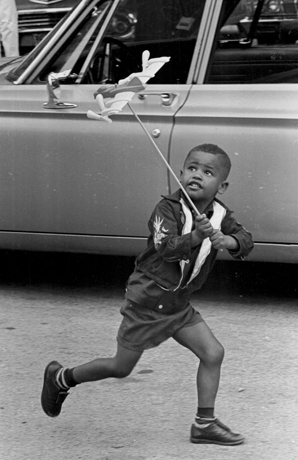 A young boy is intently focused upon his toy airplane, perched on a long stick, as he 'flies' it by running alongside a parke