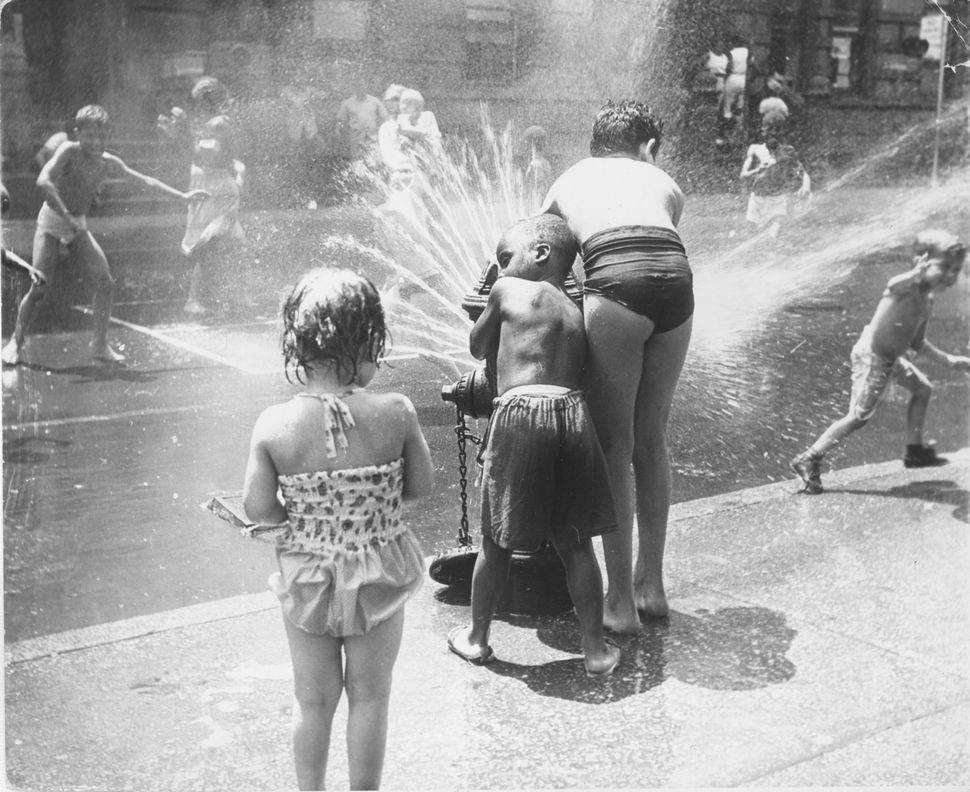Circa 1970:  Children in a New York street playing with a water hydrant.  (Photo by Peter Keegan/Keystone/Getty Images)