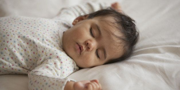 Mixed race baby girl sleeping on bed