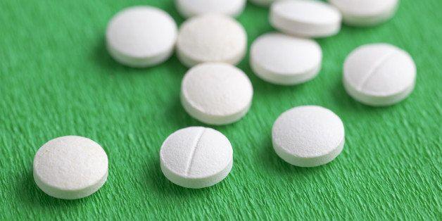 Close-Up of White Melatonin Natural Medicine Sleeping Pills on Green Background