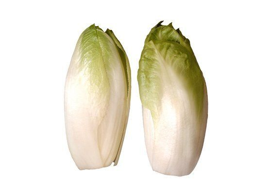 Endive (a.k.a. Belgian endive) is characterized by an elongated pointy head with very pale green tips (or dark red tips) and