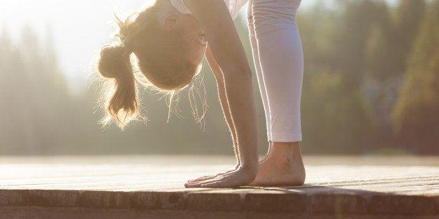 Young female sitting on dock practising yoga during sunrise/sunset.