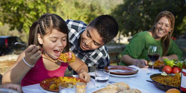 Girl trying to eat huge spoon of Paella with her brother at garden party