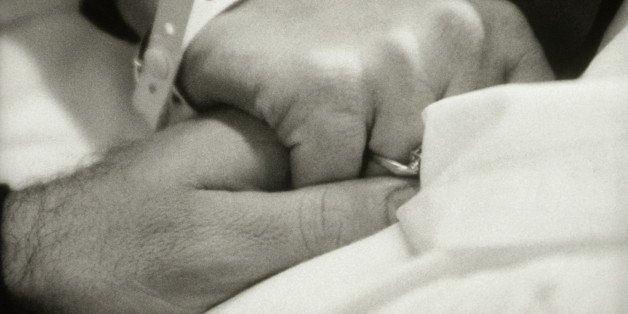 WOMAN SQUEEZING MANS HAND IN HOSPITAL