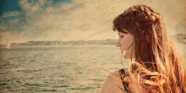 Closeup portrait of young woman in profile with one braid running along top of very windswept hair, looking down with sad expression.  Atlantic Ocean and one sailboat are in soft focus in background, overlaid with antique paper texture and wash.