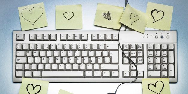 A computer keyboard covered in sticky memo notes notes with hearts drawn on them, a desk scene.