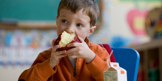 Caucasian boy eating lunch in classroom