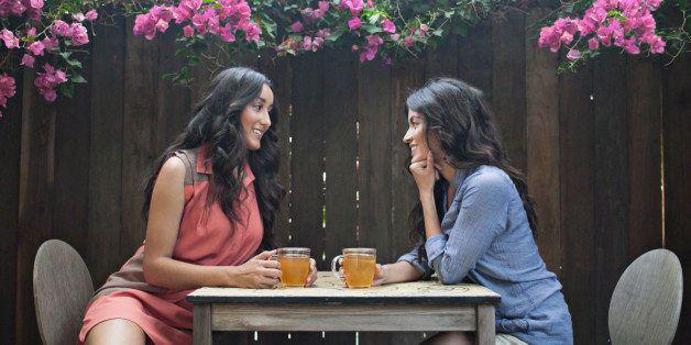 Two women having tea in back yard