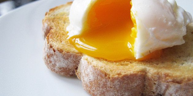A single poached egg on artisan hand sliced toasted bread. The egg is split to reveal a runny yolk. White dinner plate, non-descript dark wood table and chair just about visible in the background.