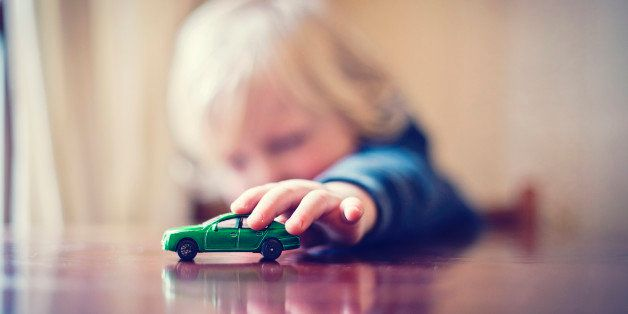 Little boy playing with toy car.