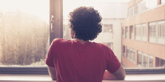 Young man is at the window silll and looking out at sunset
