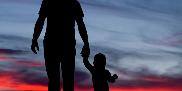 A royalty free image of a father and child holding hands and silhouetted against a sunset.