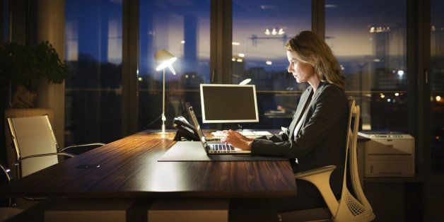 Mature business woman working late in front of a laptop.
