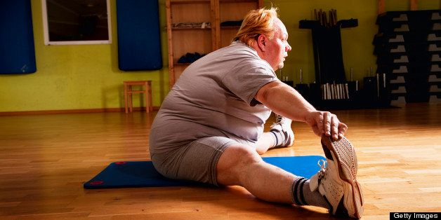 overweight man exercising stretching flexibility