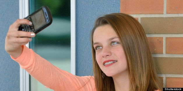 Adorable young girl, with braces, sitting in front of school building with book open on lap but taking photo of self with cell phone camera