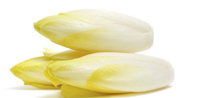 closeup of some Belgian endives on a white background.