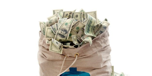 Canvas money bag with dollar symbol is overflowing with dollar bills