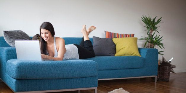 Young woman reclining on couch with laptop computer