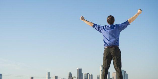 Caucasian businessman standing on urban rooftop