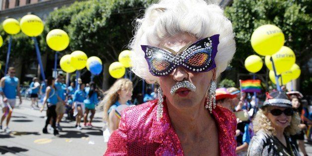 A man dressed in drag marches with a group of employees and family members with Kaiser Permanente during the 44th annual San