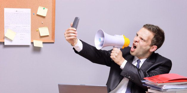 'Angry businessman in an office, shouting on a megaphone'