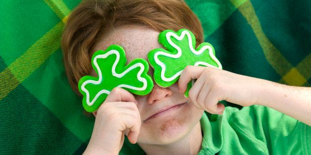 Redhead and freckle face Irish boy leprechaun with shamrock cookies over his eyes. Smiling Irish child wearing green on St. Patrick's. (SEE LIGHTBOXES BELOW for more holdiday food and people backgrounds...)